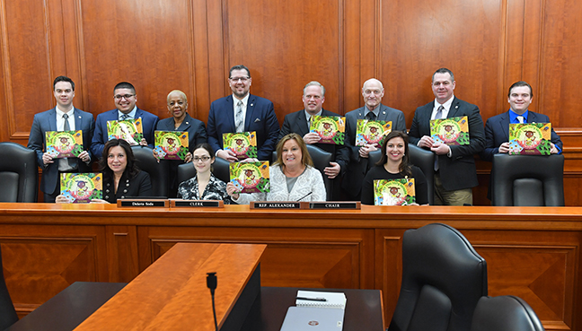 State Rep. Angela Witwer (D-Delta Township) and other members of the House Agriculture Committee show off a farm-to-table children's book from the Michigan Farm Bureau in honor of March is Reading Month, Wednesday, February 20, 2019.
