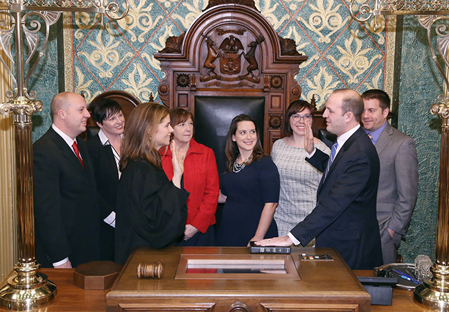 State Rep. Kevin Hertel (D-St. Clair Shores) takes the oath of office from Michigan Supreme Court Justice Bridget Mary McCormack at the swearing-in ceremony for the official opening of the 99th session of the Michigan House of Representatives on Jan. 11, 2017. With him are his brother state Senator Curtis Hertel Jr. and his wife Elizabeth, his mother Vickie Hertel, his wife, Ann, and staff Kelly Stec and Alex Dobbins.