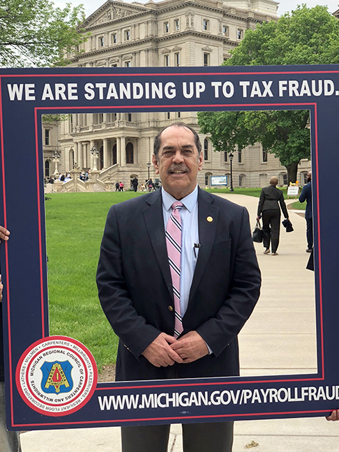 State Rep. Tim Sneller (D-Burton) stands up to payroll and tax fraud at the state Capitol on May 23, 2019.