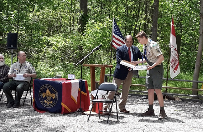 State Rep. Tim Sneller (D-Burton) gives Remington Claussen a State of Michigan Tribute and a U.S. Flag at his Eagle Scout Court of Honor ceremony at YMCA Camp Copneconic in Fenton, on June 2, 2019.