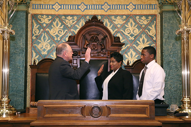 Tenisha Yancey takes the oath of office at the state Capitol in Lansing on Friday, Nov. 17, 2017. Rep. Yancey is joined by her son Jaylen.