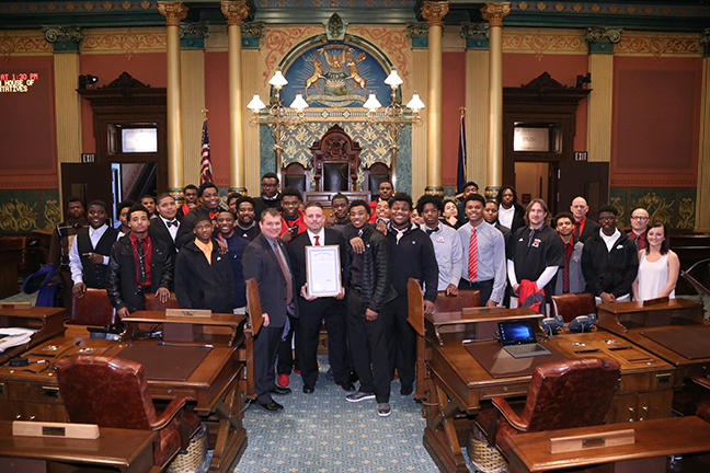 State Rep. Terry Sabo (D-Muskegon), first row left with Muskegon High School Football Coach Shane Fairfield (next to Sabo holding tribute) and the Muskegon High School Big Reds Division III champion football team members at the state Capitol in Lansing on Tuesday, Jan. 30, 2018.