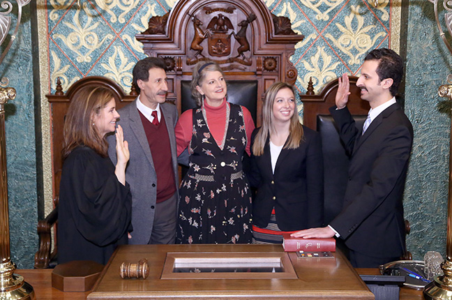 State Rep. Yousef Rabhi (D-Ann Arbor) takes the oath of office from Michigan Supreme Court Justice Bridget Mary McCormack at the swearing-in ceremony for the official opening of the 99th Legislature of the Michigan House of Representatives on Jan. 11, 2017. Pictured with Rep. Rabhi are his parents, Peggy and Lounes Rabhi, and girlfriend Lizzie Nash.