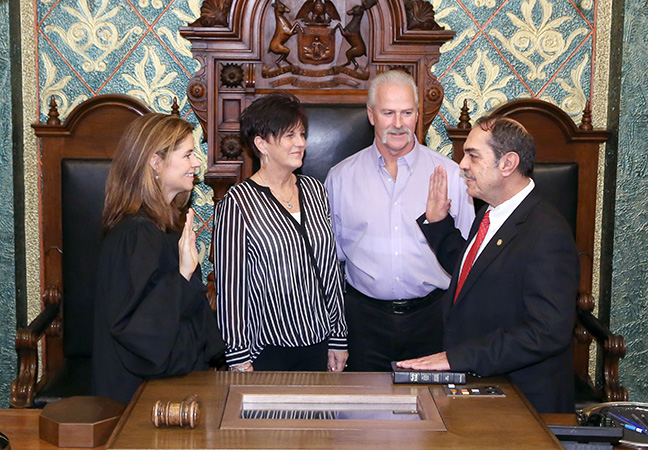 State Rep. Tim Sneller (D-Burton) takes the oath of office from Michigan Supreme Court Justice Bridget Mary McCormack at the swearing-in ceremony for the official opening of the 99th Legislature of the Michigan House of Representatives on Jan. 11, 2017. Pictured with Rep. Sneller is his sister Sandi Twite and brother-in-law Don Twite.