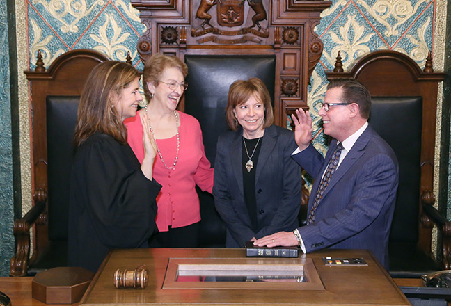 State Rep. William Sowerby (D-Clinton Township) takes the oath of office from Michigan Supreme Court Justice Bridget Mary McCormack at the swearing-in ceremony for the official opening of the 99th session of the Michigan House of Representatives on Jan. 11, 2017. With him are Linda Pidutti, a family friend, and his wife Dr. Martha Higgins.