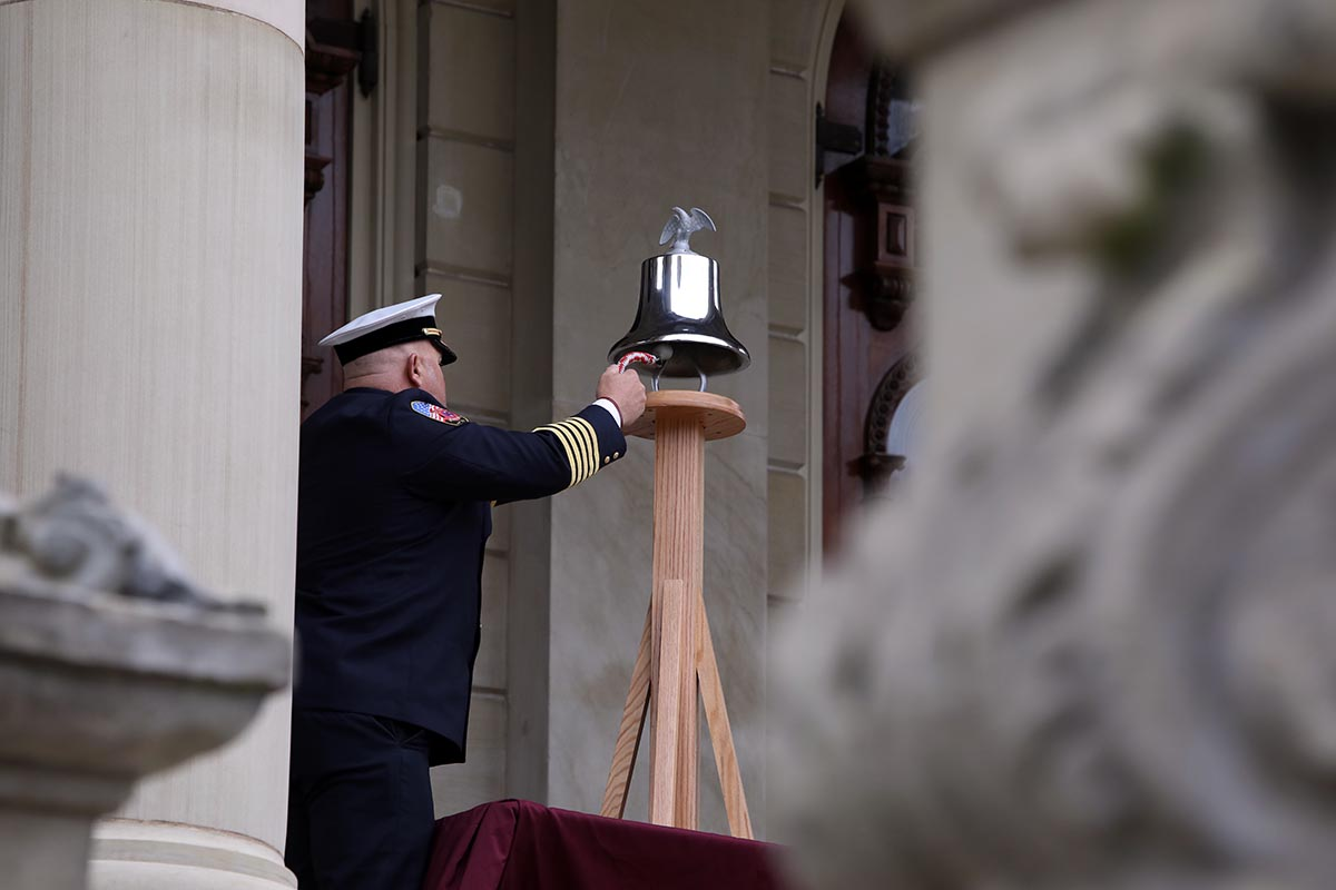 A member of the honor guard performs the traditional tolling of the bell to honor those lost during 9/11 memorial ceremony at the Capitol on Sept. 10, 2020.