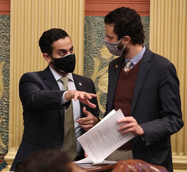 State Rep. Abraham Aiyash (D-Hamtramck) discusses legislation with Democratic Floor Leader Yousef Rabhi (D-Ann Arbor) on the House floor on December 2, 2020.