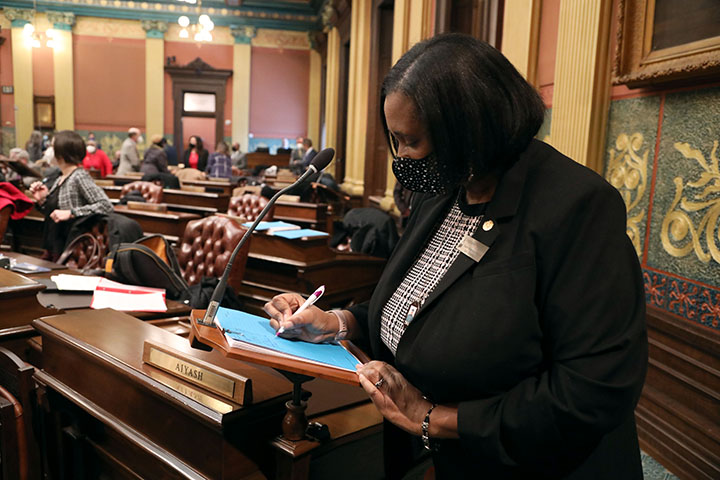 State Rep. Stephanie A. Young (D-Detroit) signs her name in support of a bill while working on the House floor January 26, 2021.