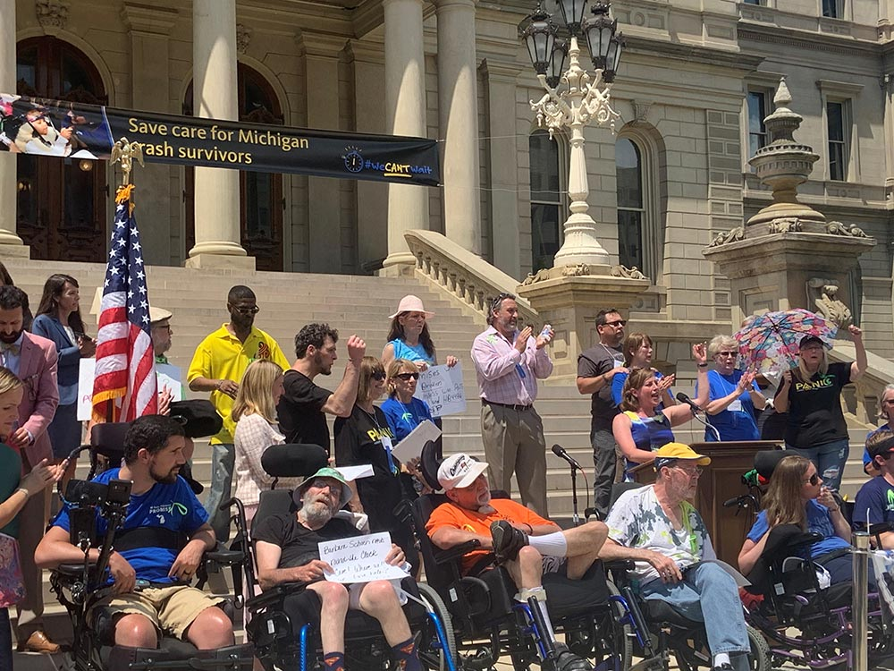 State Rep. Julie Rogers (D-Kalamazoo), seen at the podium, speaks during a rally on June 9 at the state Capitol in Lansing to protect care for auto accident victims.